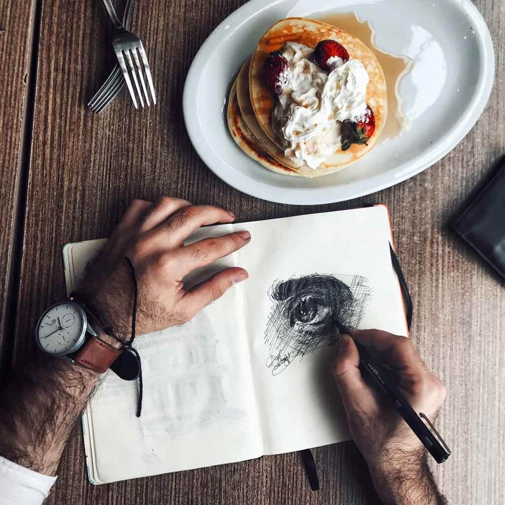 Photo of a man drawing in a sketchbook with a plate of pancakes nearby.