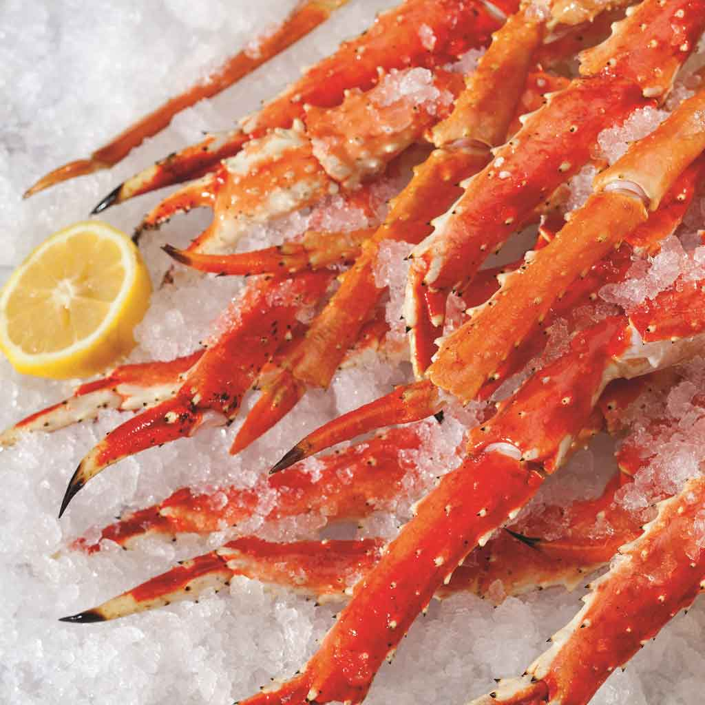 Closeup of a pile of crab legs on ice.