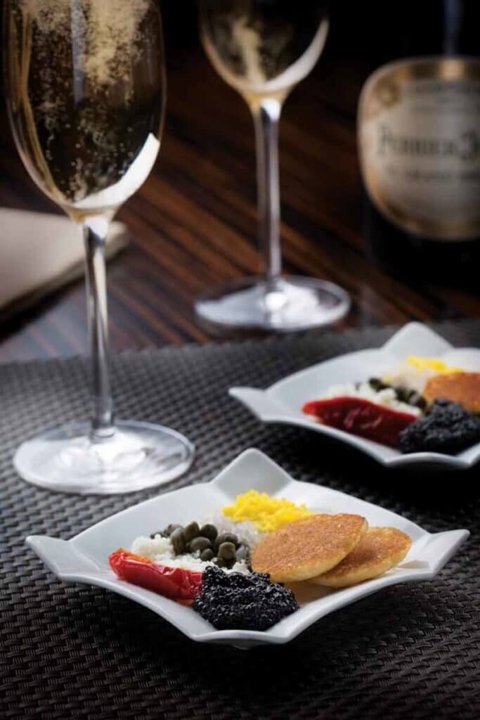 Closeup of 2 plates of caviar and accompaniments and 2 glasses of champagne.
