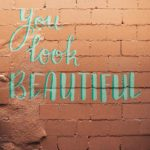 "Photo of a peachy pink brick wall with the phrase ""You look beautiful,"" painted on it."