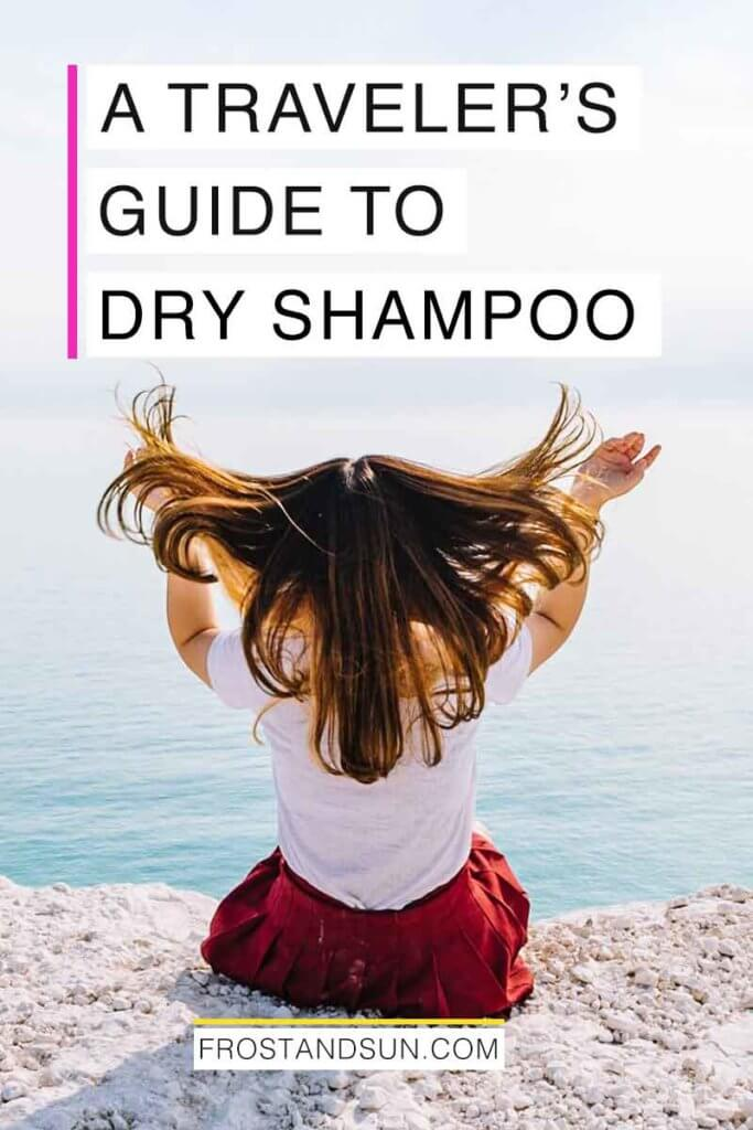 "Photo of woman sitting on a cliff overlooking the ocean with her back to the camera, flipping her hair in the air.Overlying text reads ""A Traveler's Guide to Dry Shampoo."""