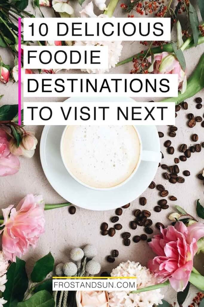 "Flatlay photo of a latte on a saucer with pink and white flowers surrounding it and scattered coffee beans. Overlying text reads ""10 Delicious Foodie Destinations to Visit Next."""