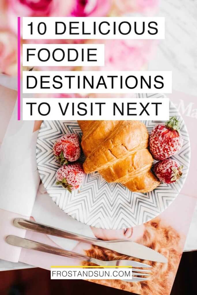 "Flatlay of a marble counter with pink flowers, a fashion magazine, and a plate with a croissant and strawberries. Overlying text reads ""10 Delicious Foodie Destinations to Visit Next."""