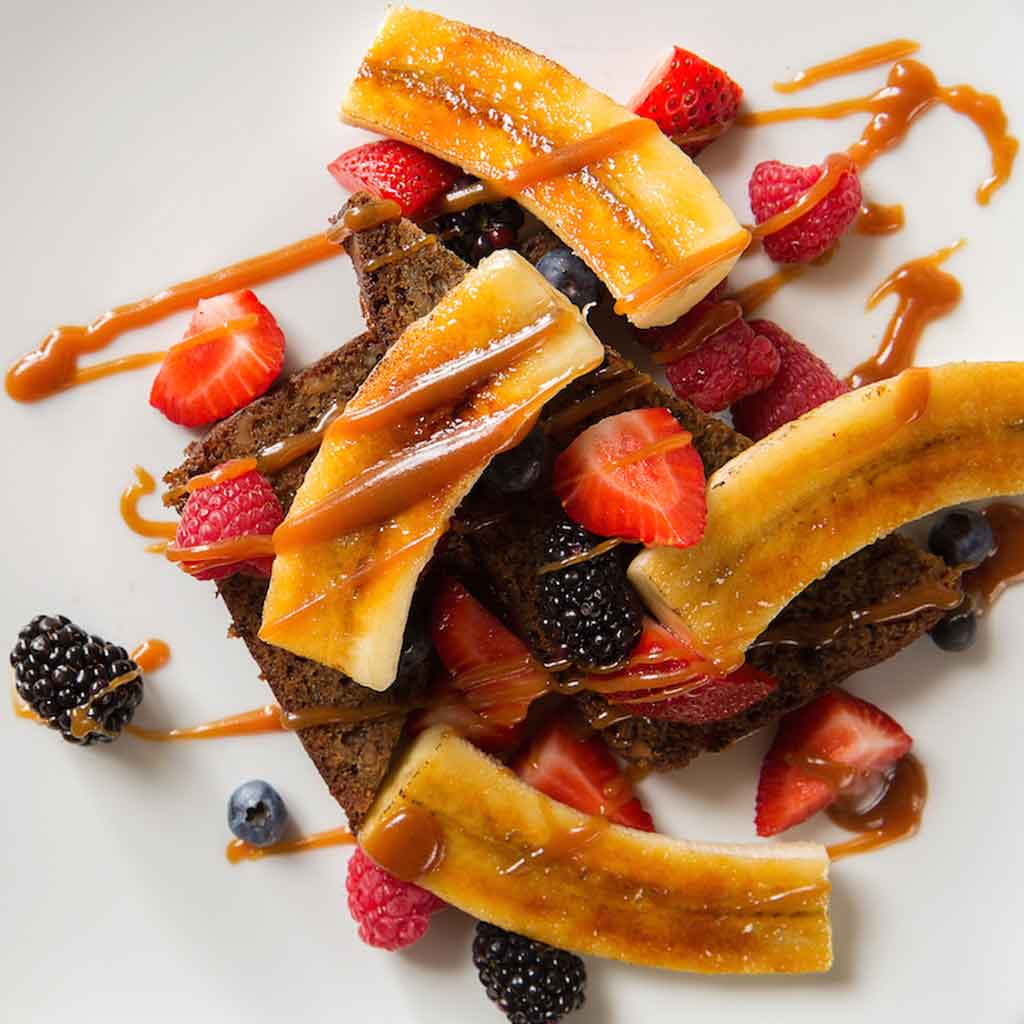 Photo of a plate of banana french toast with berries.
