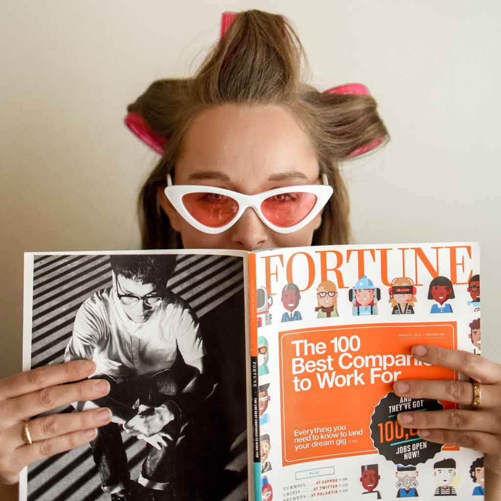 Photo of a woman with velcro rollers in her hair holding up a Fortune magazine in front of her.