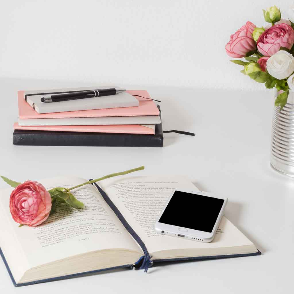 Photo of an open book with an iphone resting on it. Nearby is a stack of journals and a vase of flowers.