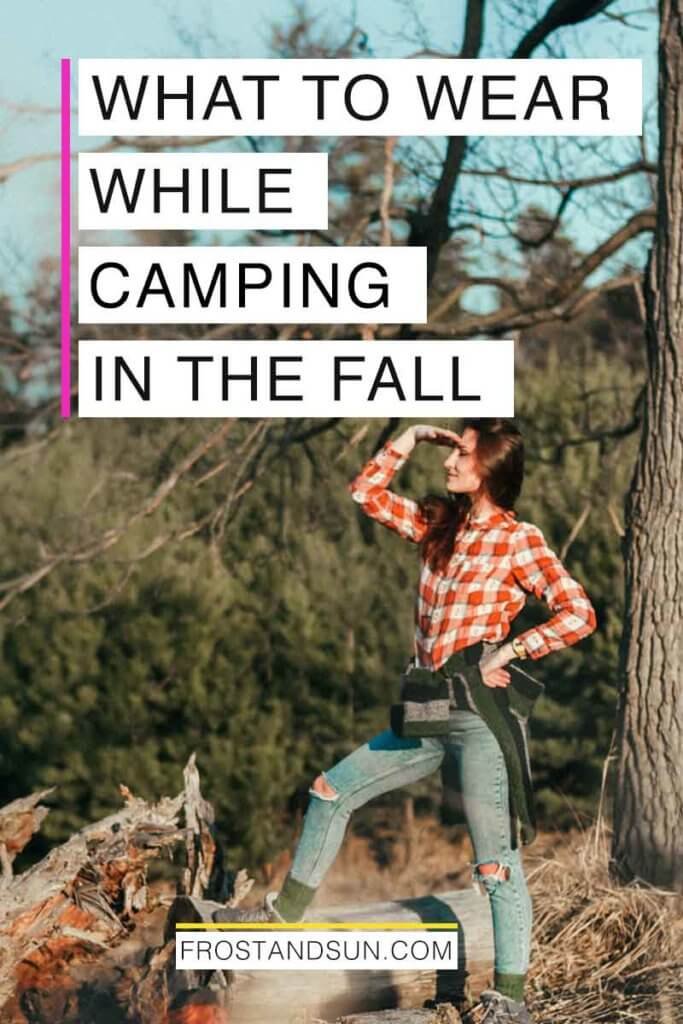 "Photo of a woman standing outdoors wearing a plaid flannel shirt and jeans. Overlying text reads ""What to Wear While Camping in the Fall."""