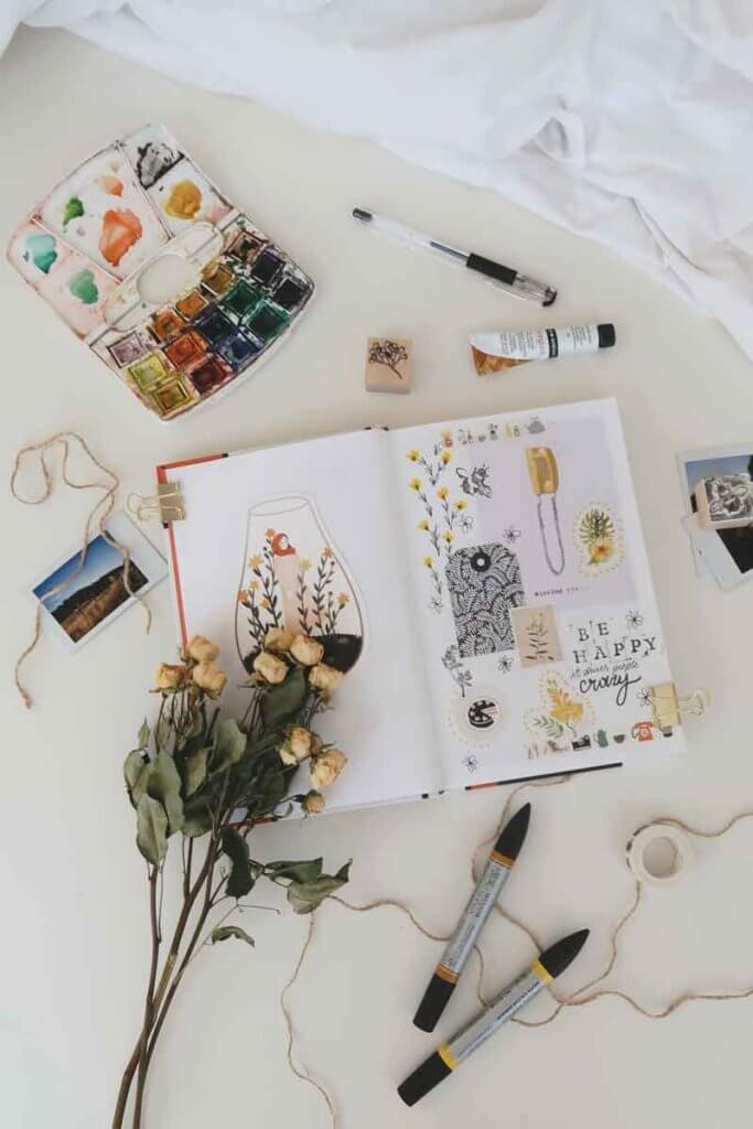 Flat lay photo of a scrapbook surrounded by craft and art supplies.