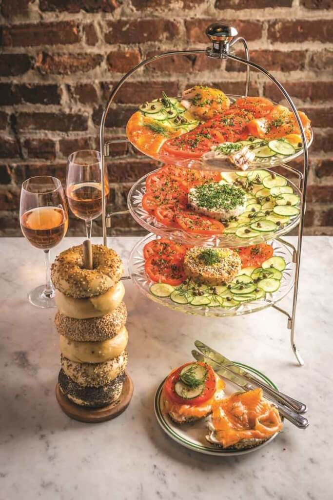 Photo of a tower of bagels next to a tower of vegetables and schmear, alongside 2 glasses of rosé wine.