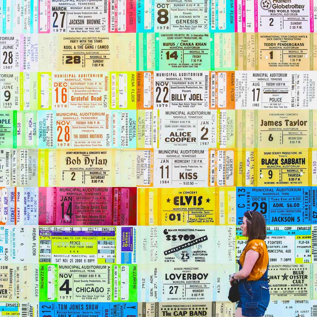 Photo of a woman walking by a wall plastered in giant replicas of concert ticket stubs.
