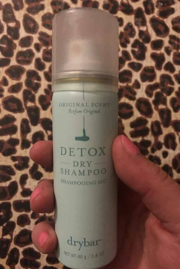 Photo of a hand holding a small can of drybar Detox dry shampoo.