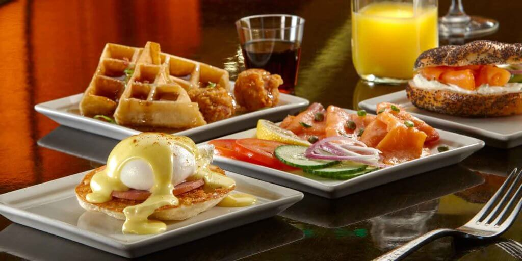 Photo of a spread of breakfast foods, like eggs benedict, waffles, and a bagel with lox.