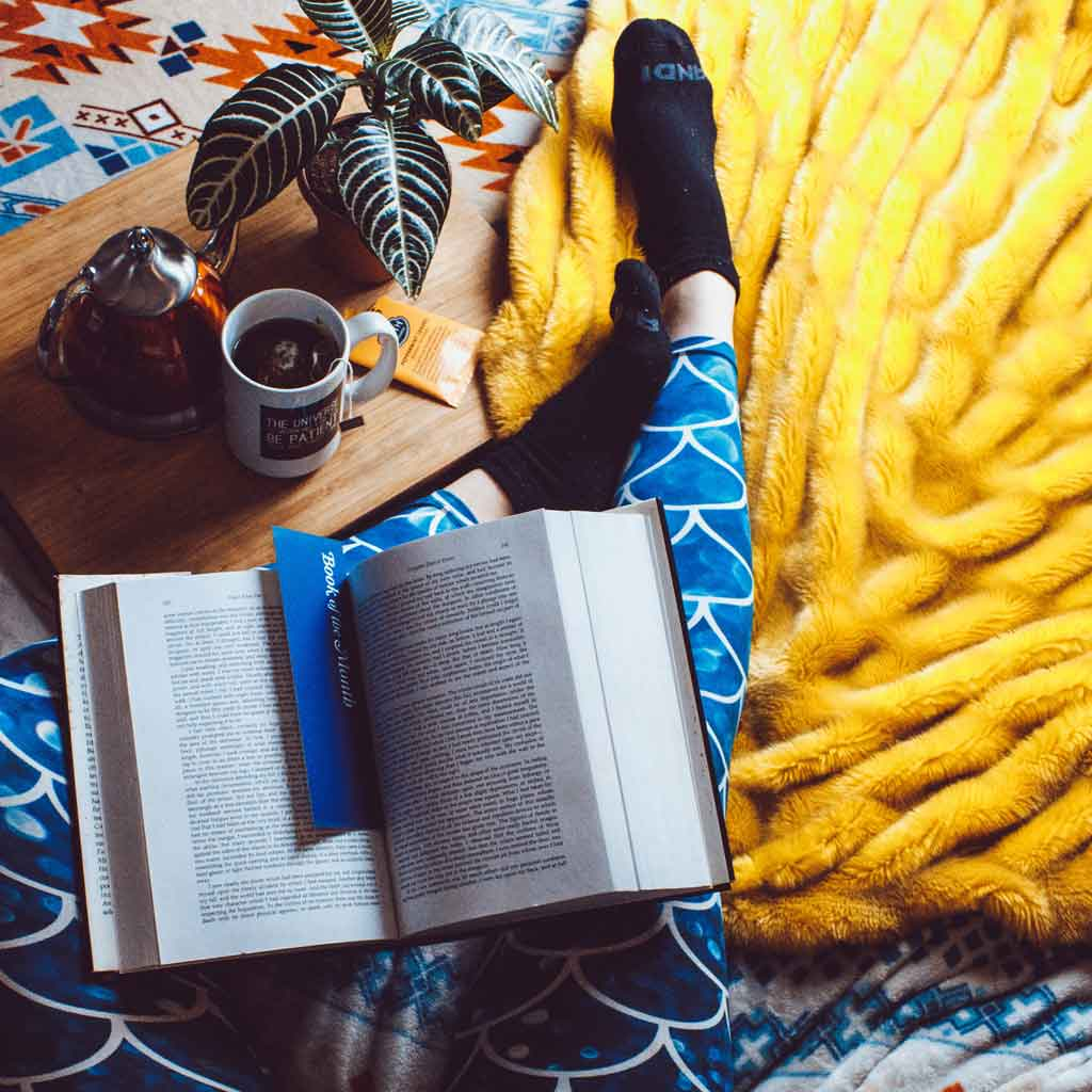 Flatlay photo of a woman's legs with a book on her lap, a large fluffy blanket, and a wooden tray with a cup of tea nearby.
