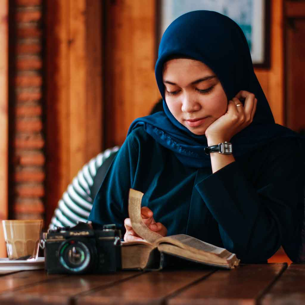 Photo of a woman in a hijab reading a book at a cafe.