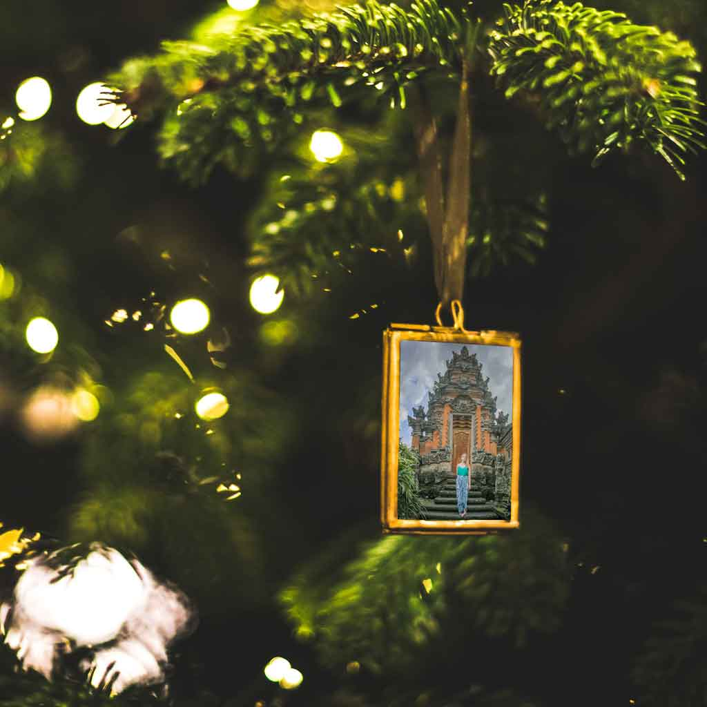Closeup of a photo framed ornament on a Christmas tree.