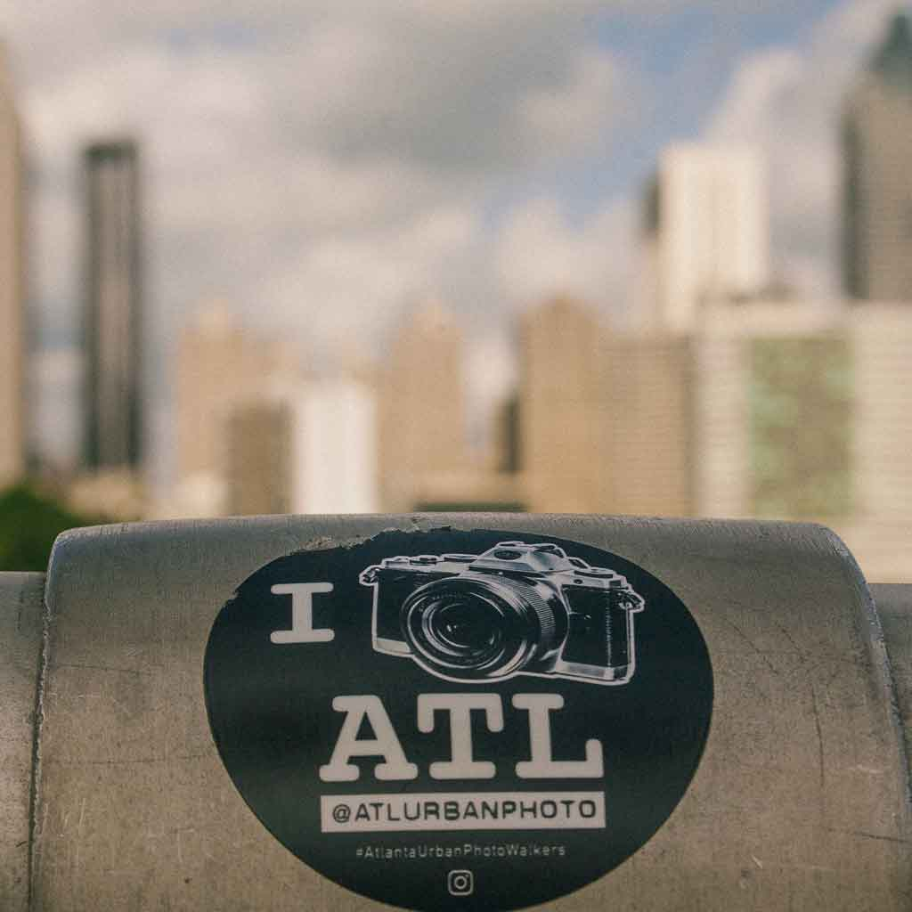 Close up of a sticker on a railing that reads I [picture of camera] ATL.""