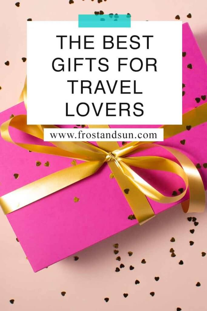 "Overhead view of a gift wrapped in bright pink wrapping paper with gold heart confetti sprinkled around. Overlying text reads ""The Best GIfts for Travel Lovers."""