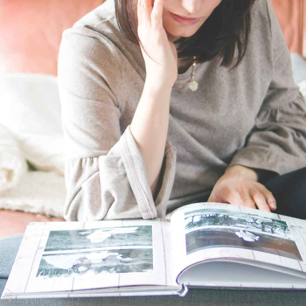Photo of a woman looking at a photo book.