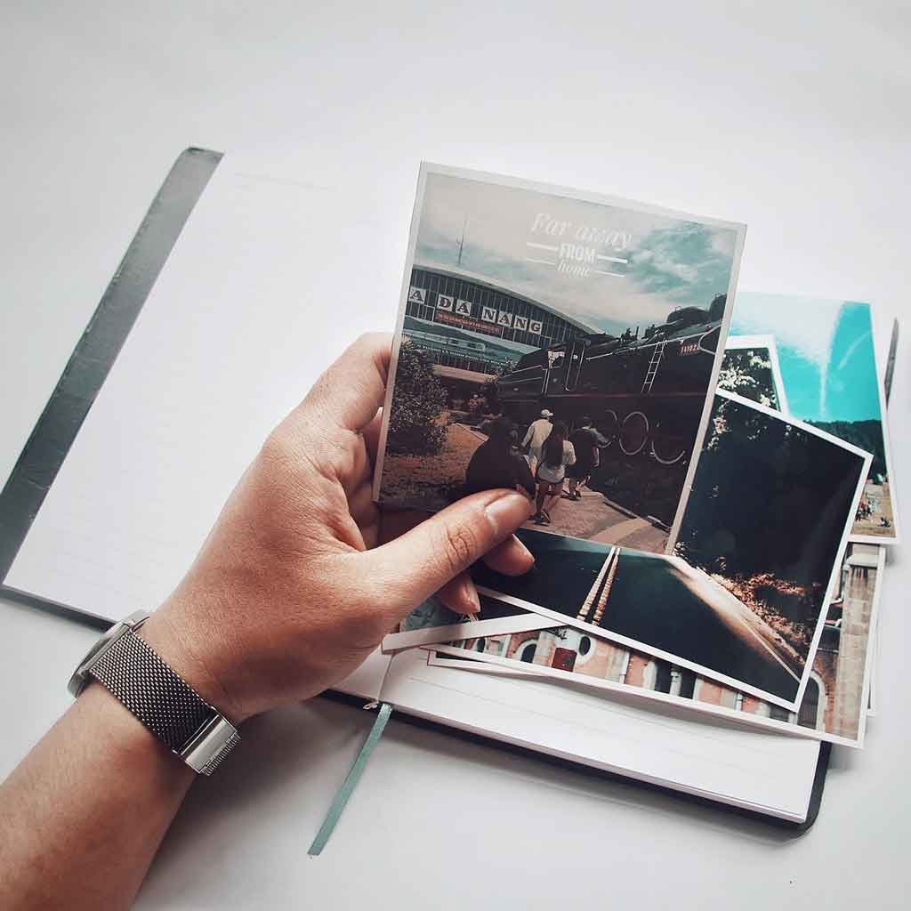 Photo of a person holding a printed photo above a notebook and pile of other photos.