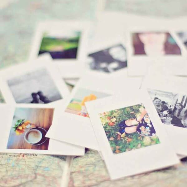 Closeup of a pile of printed Instax photos on top of a map.