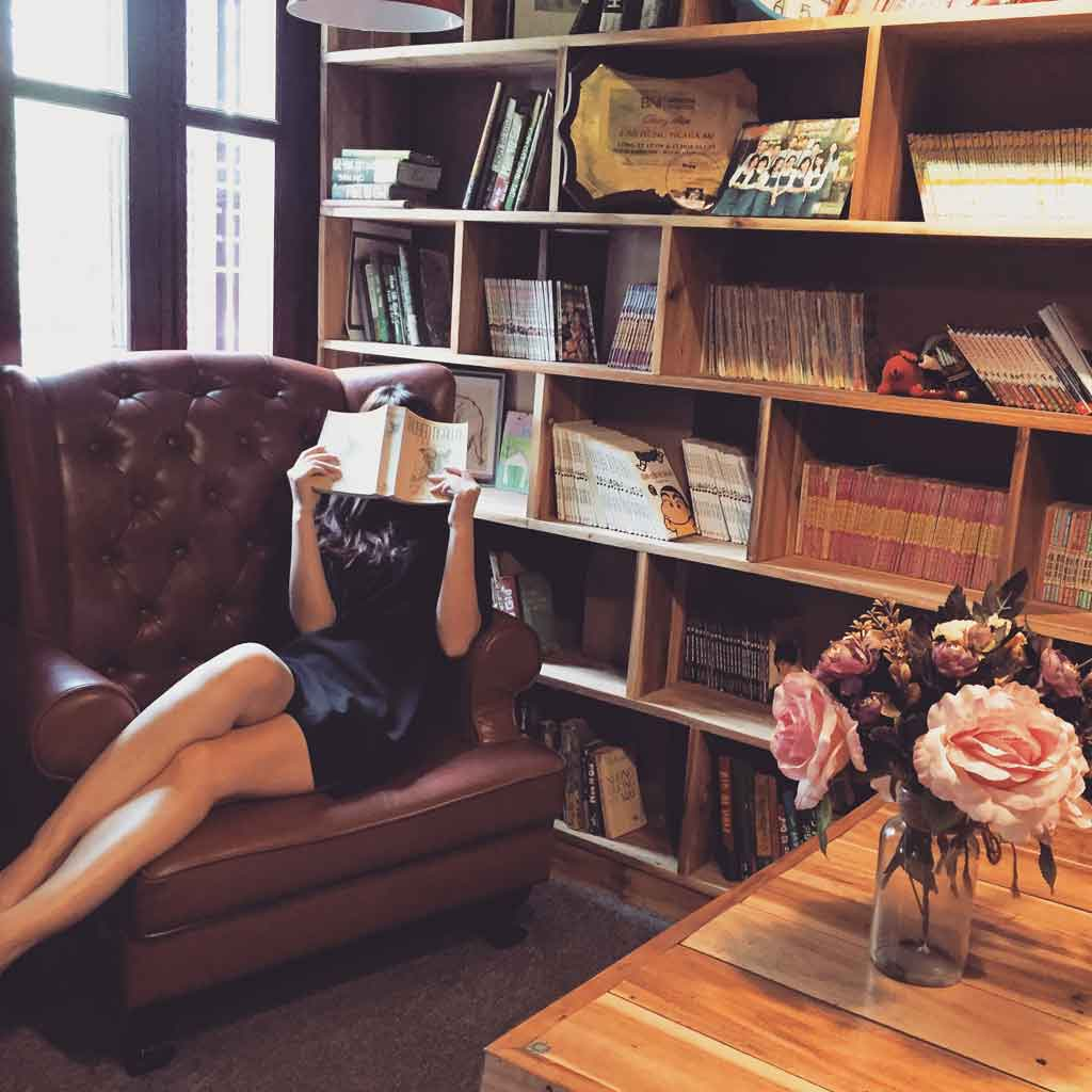 Photo of a woman sitting on a leather chair while reading a book in a library.