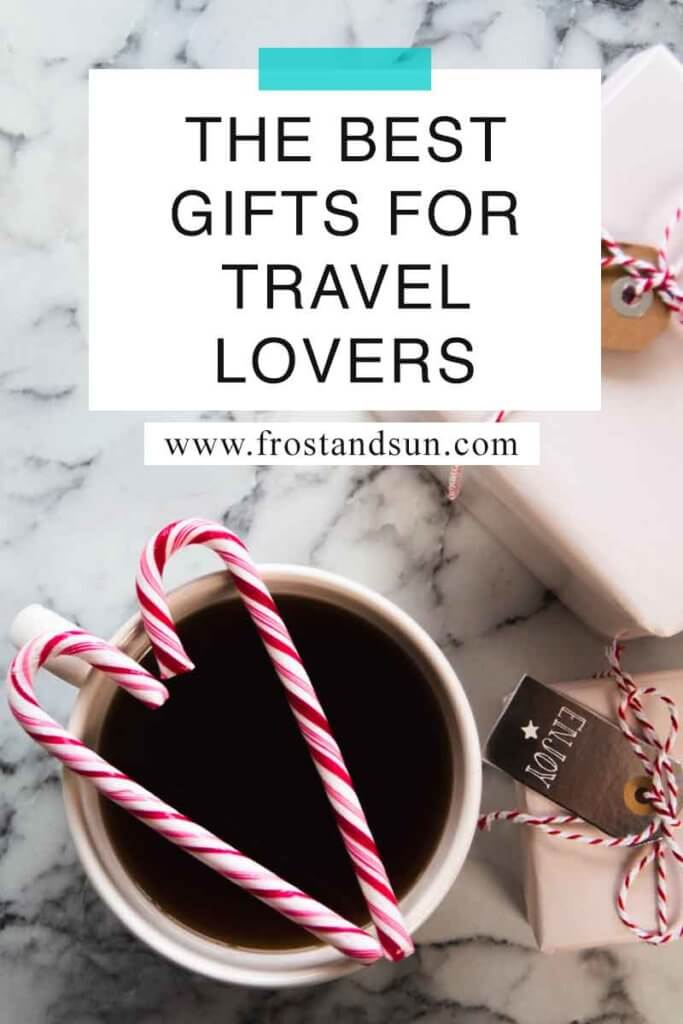 "Flat lay photo of a cup of coffee with candy canes resting on top and wrapped gifts nearby. Overlying text reads ""The Best Gifts for Travel Lovers."""