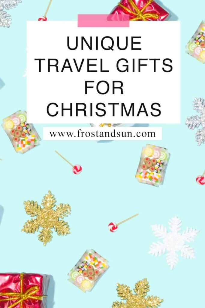 "Flat lay photo of glitter covered snowflakes and miniature wrapped gifts on an aqua background. Overlying text reads ""Unique Travel Gifts for Christmas."""