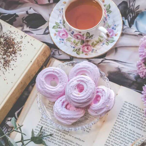 Flatlay photo of old books with a bunch of lavender flowers, pink meringue cookies, and a cup of tea.