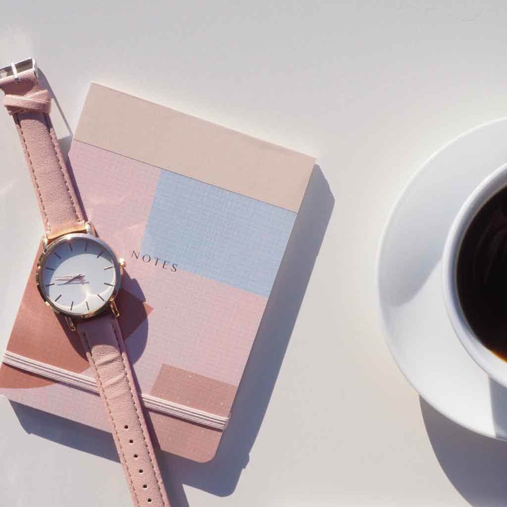 Flat lay photo of a pink and gray notebook on a table with a watch strewn on top and a cup of coffee nearby.