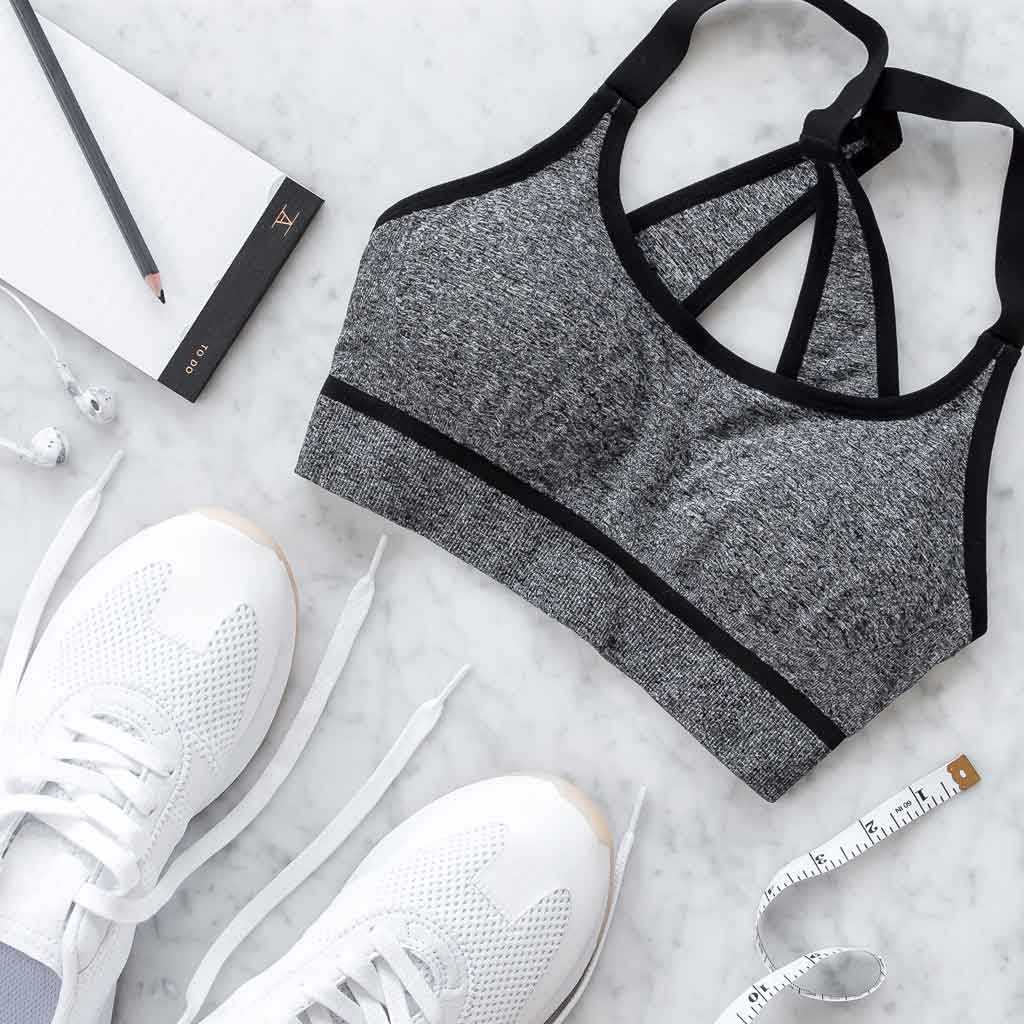 Flat lay photo of a grey and black sports bra, white sneakers, ear buds, measuring tape, and a notepad and pencil.