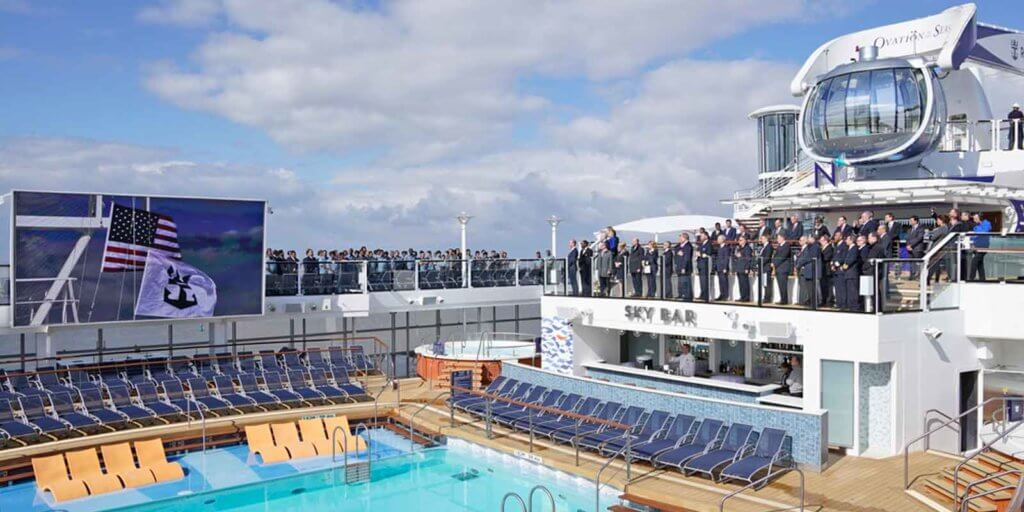 Closeup photo of the dedication ceremony for Royal Caribbean International's Ovation of the Seas cruise ship. People in suits and business attire are standing on the top deck of the ship watching a flag raising ceremony on a large flat screen above the pool area below them.