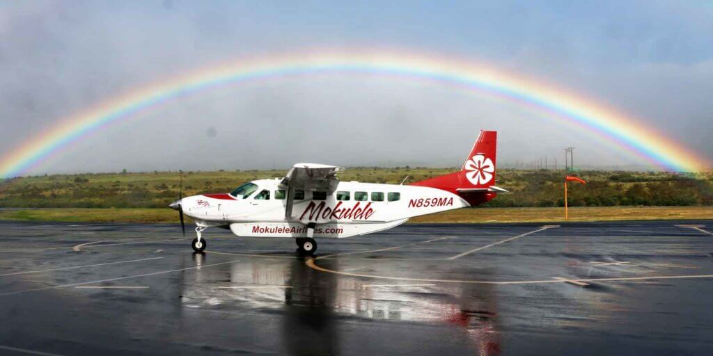 Photo of a Cessna passenger plane at a small airfield with a rainbow overhead. The Plane says Mokulele and MokuleleAirlines.com on the side in the color red.