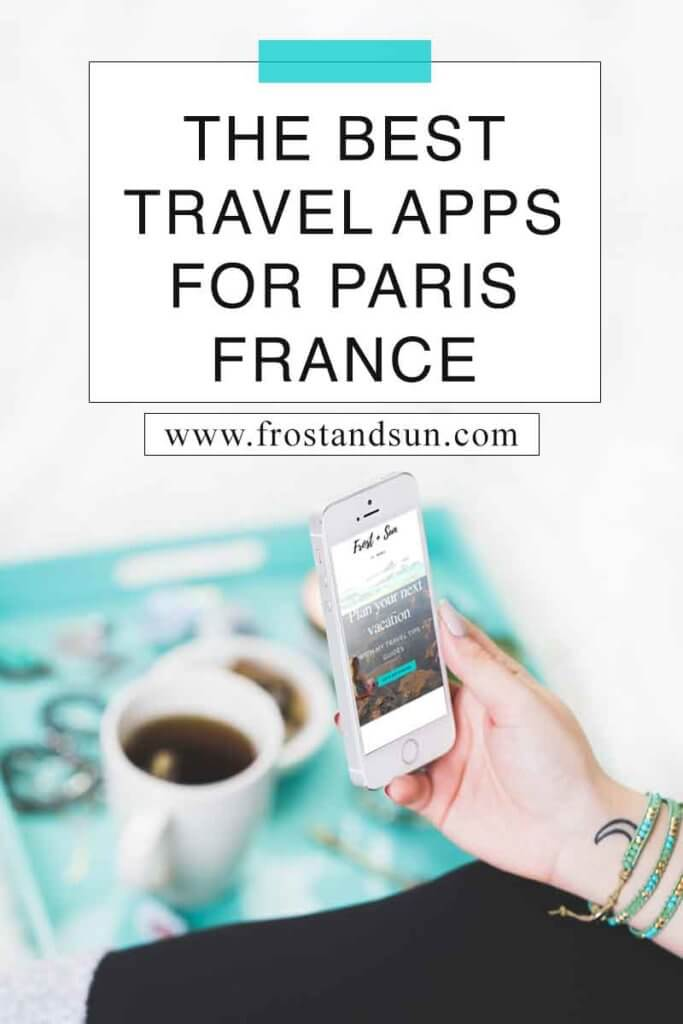 "Closeup of a person holding a phone showing the Frost + Sun travel blog homepage. In the background is a turquoise tray with coffee, jewelry, and assorted items. Overlying text reads ""The Best Travel Apps for Paris France."""
