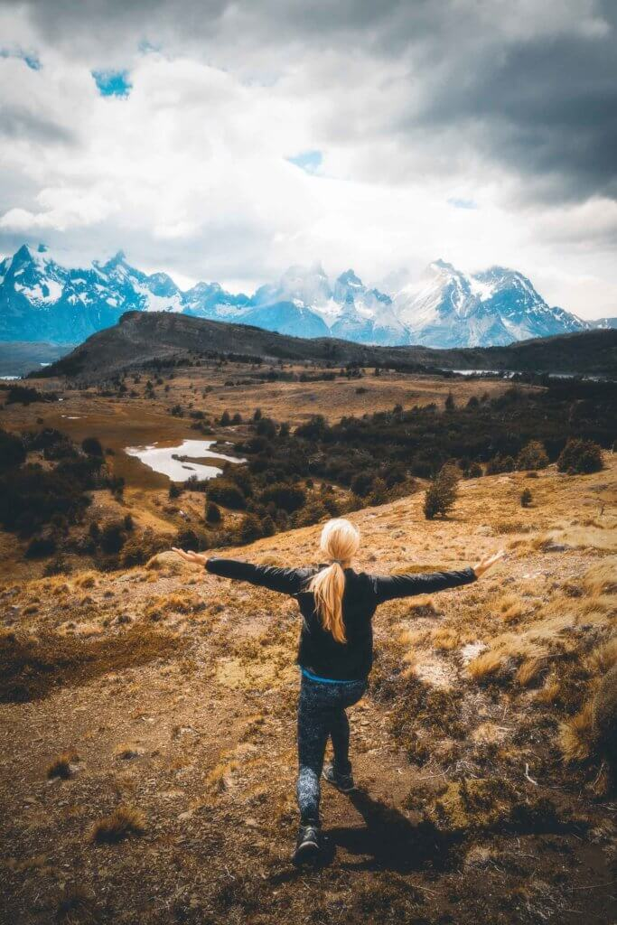 Landscape view of a woman with her arms outstretched while overlooking the landscape and mountains in Patagonia.