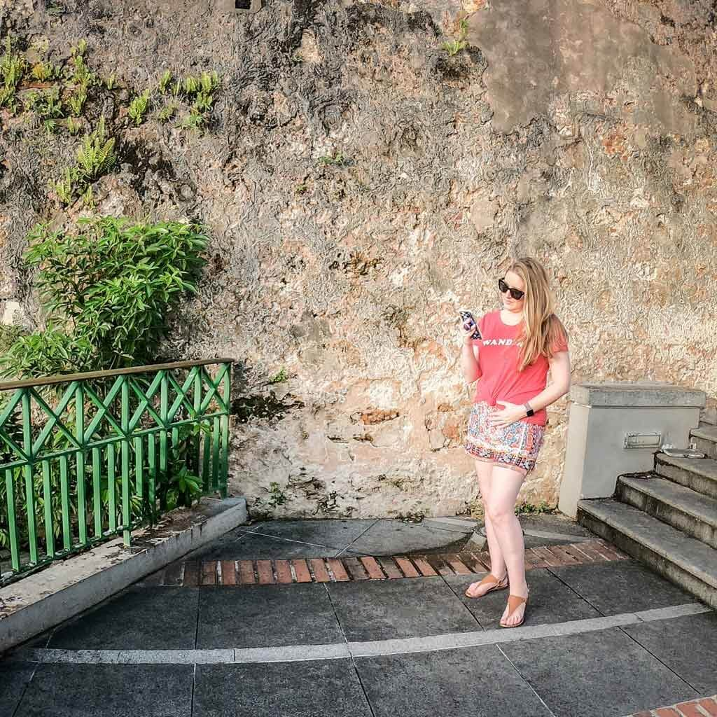Photo of Meg Frost standing in front of a stone wall while looking at her phone.