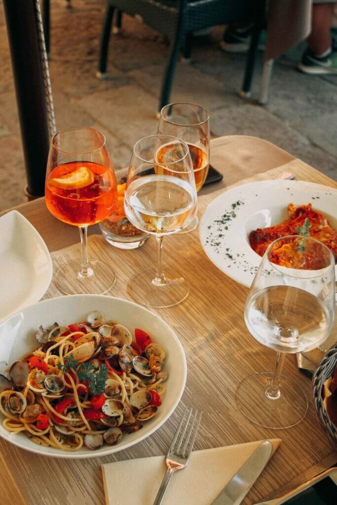 Closeup of a small table with 2 Italian pasta dishes and several wine glasses filled with a drink.