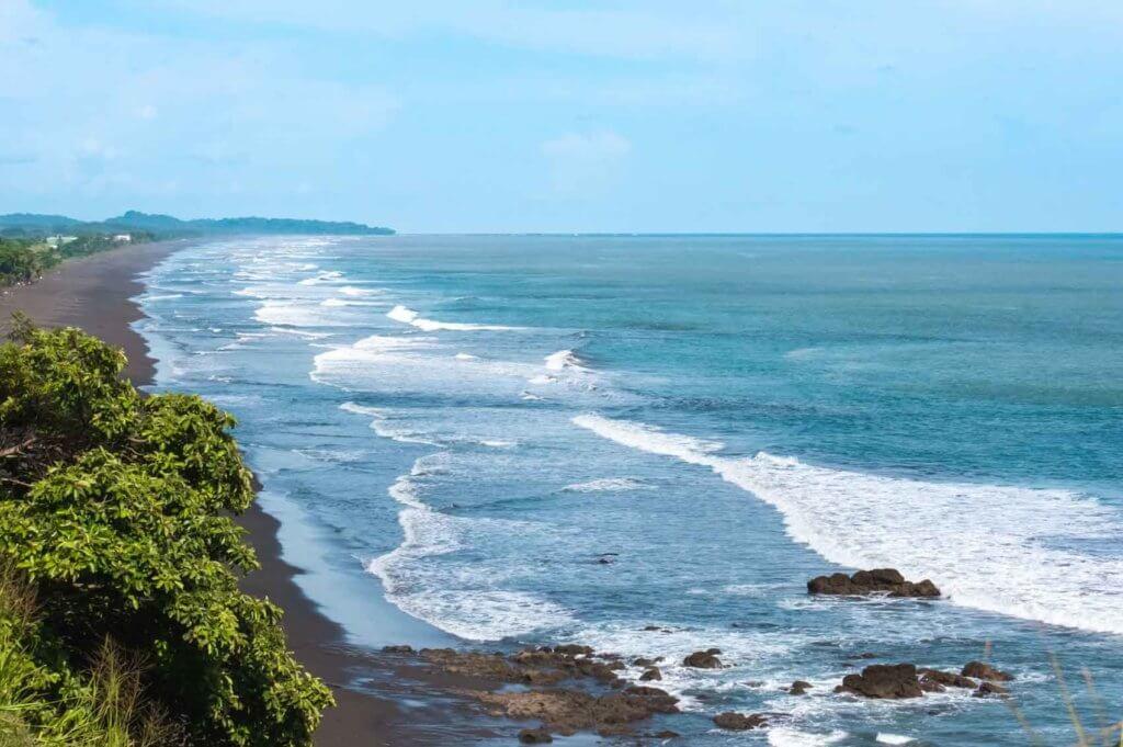 Aerial landscape view of a black sand beach in Costa Rica.