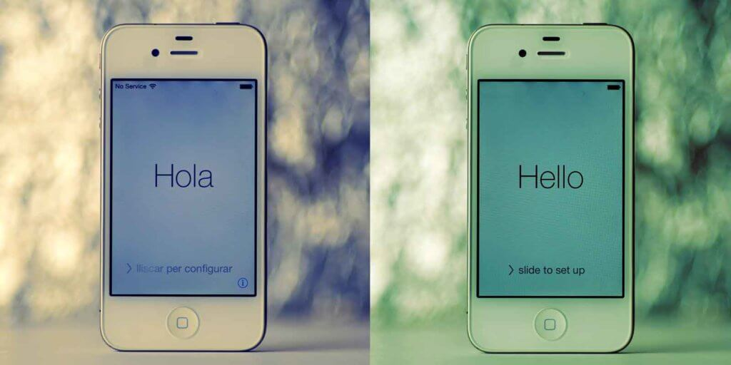 Composite photo of 2 white iPhones in Spanish and English, one that says Hola and one that says Hello.
