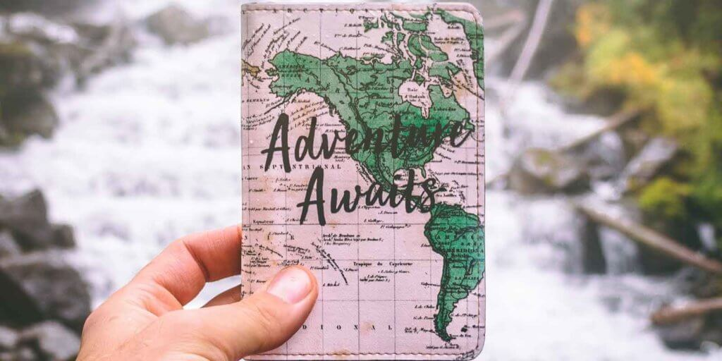 "Closeup of a person holding a passport cover with an image of a map and the words ""Adventure Awaits."""