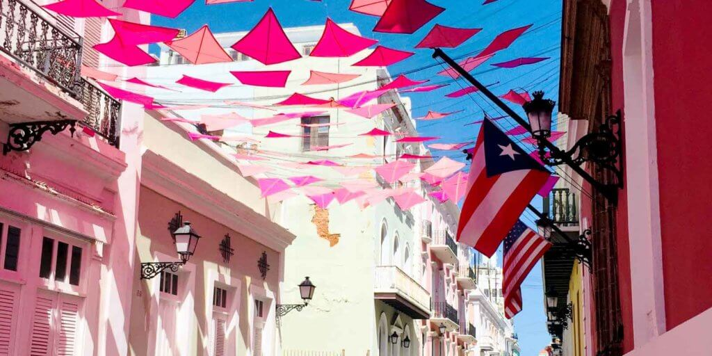 Closeup of pink kites strung up between 2 buildings, with the US and Puerto Rico flags in the distance.