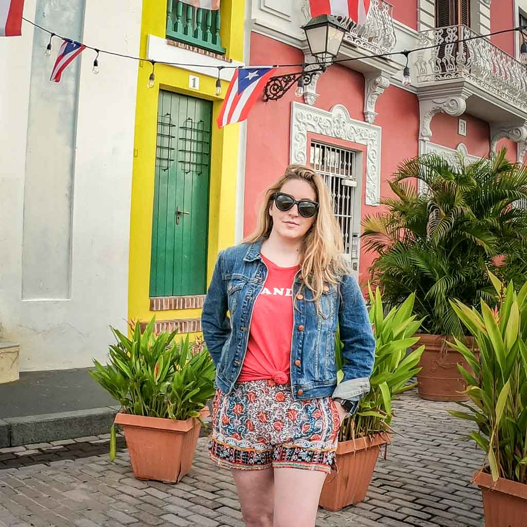 Photo of travel blogger Meg Frost standing in front of colorful buildings with small Puerto Rico flags strung up along a string of lights.