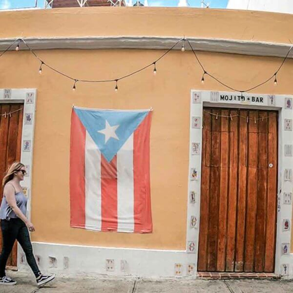 Photo of Meg Frost in a flowy tank top and jeans walking by a golden yellow building with the flag of Puerto Rico hanging on it.