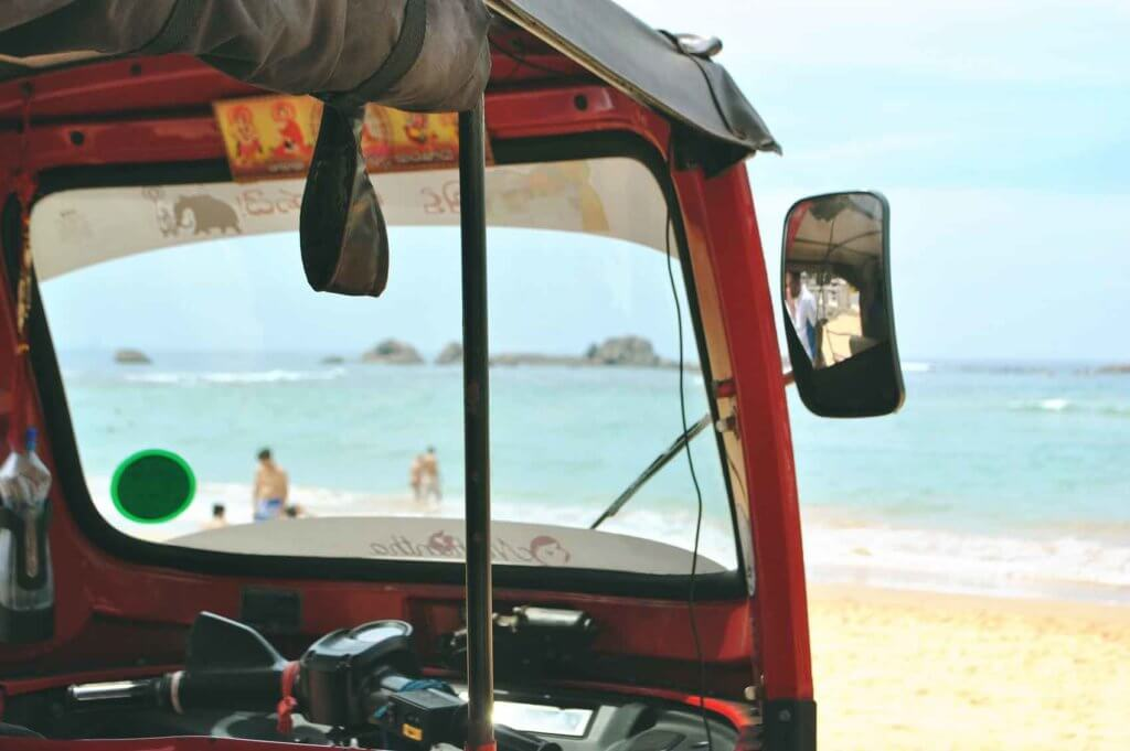 Closeup of a tuk tuk vehicle parked while looking out to a beach and ocean.