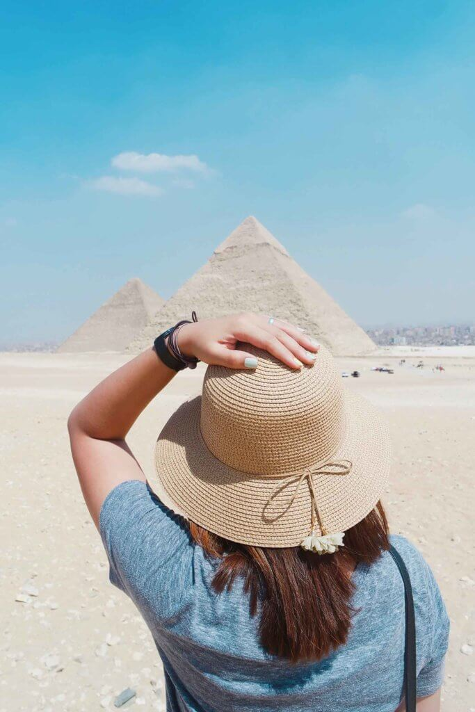 A woman standing with her back to the camera with her hand on her straw hat. In the background are the Great Pyramids of Egypt.