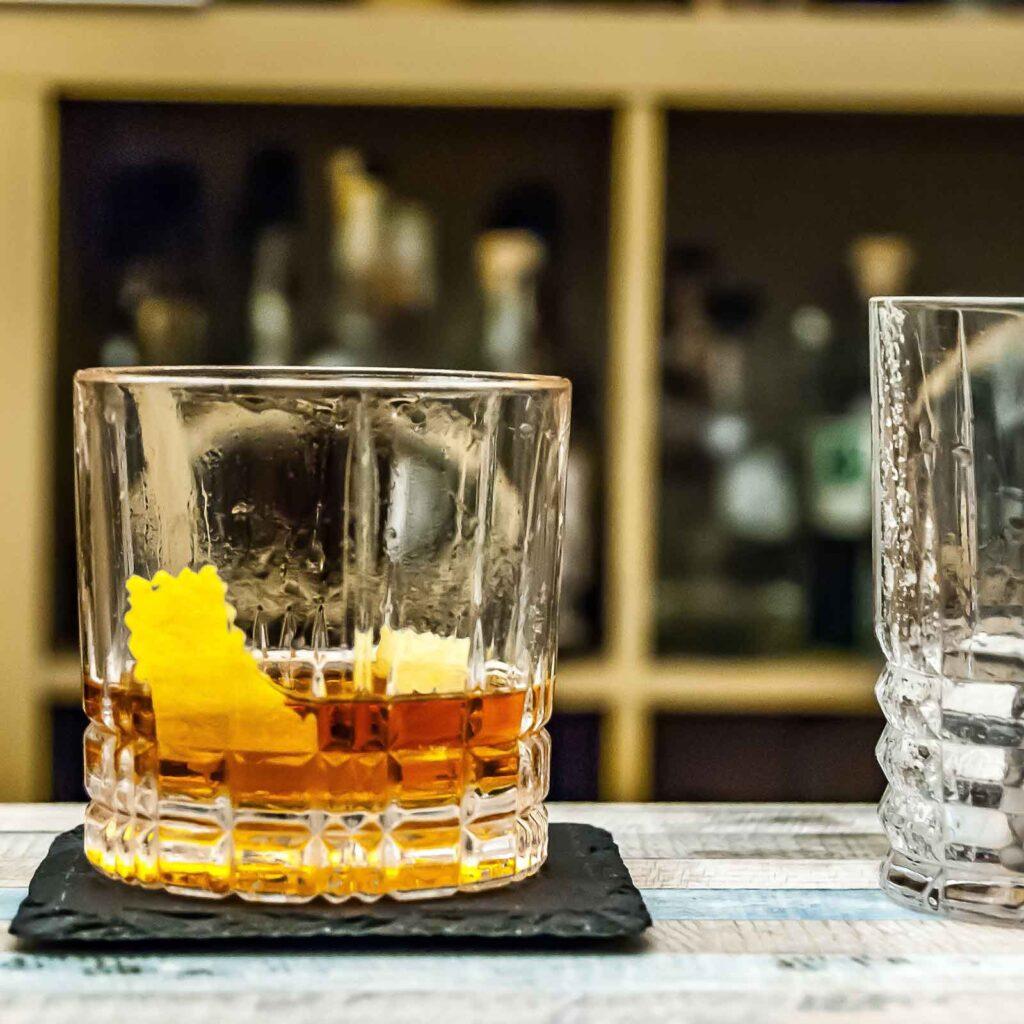 Closeup of a classic Sazerac cocktail on top of a black stone coaster on a bar.