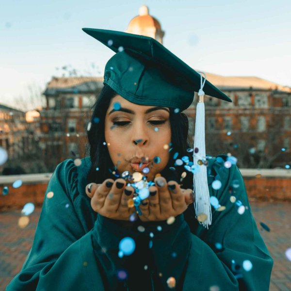 Closeup of a young black woman in dark green graduation cap and gown. She is blowing confetti from her hands toward the camera.