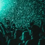 Closeup of a crowd of people in a dark venue with teal lights and confetti falling from above.