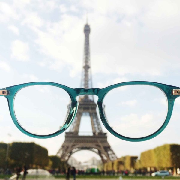 Photo of the Eiffel Tower through a pair of turquoise glasses held in front of the camera.