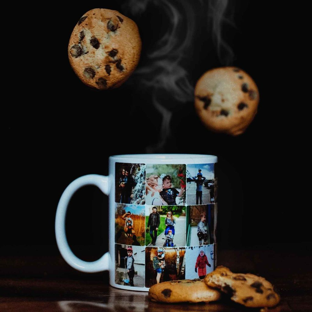 Photo of a mug with photos printed on it. Chocolate chip cookies are arranged next to the mug with another 2 cookies falling from above.