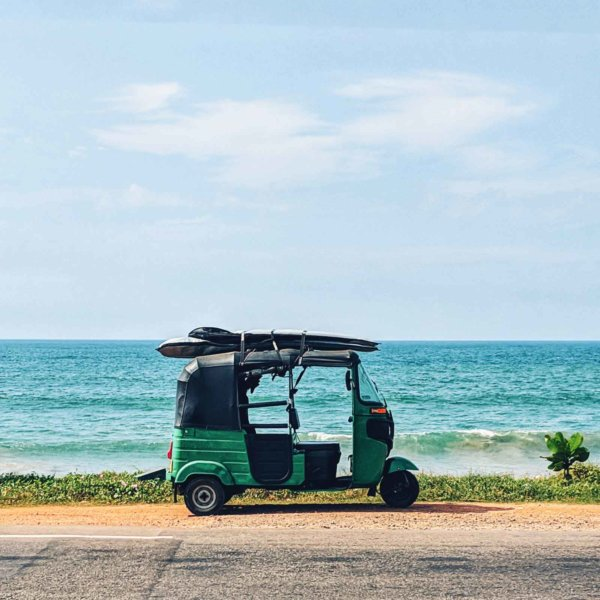 Photo fo a green tuk tuk parked on the side of the road with the ocean in the background.